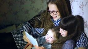 Mãe e crianças com um tablet pc em casa que olham desenhos animados e jogo video estoque