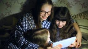 Mãe e crianças com um tablet pc em casa que olham desenhos animados e jogo filme