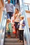Mãe e crianças na escada rolante no shopping Fotografia de Stock Royalty Free