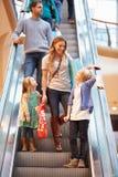 Mãe e crianças na escada rolante no shopping Imagens de Stock
