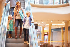 Mãe e crianças na escada rolante no shopping Fotos de Stock