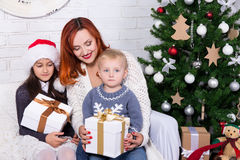 Mãe e crianças que abrem caixas de presente na frente do Natal foto de stock