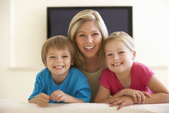 Mãe e crianças que olham a tevê do tela panorâmico em casa Imagem de Stock