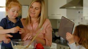 Mãe e crianças que preparam o alimento na cozinha video estoque