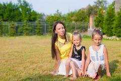 Mãe e crianças que sentam-se fora em bonito fotografia de stock