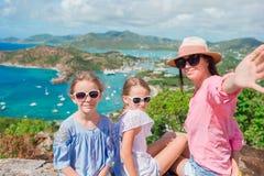 Mãe e crianças que tomam o selfie com vista do porto inglês de Shirley Heights, Antígua, baía do paraíso na ilha tropical imagens de stock royalty free