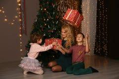 Mãe e crianças que trocam e que abrem presentes de Natal Foto de Stock