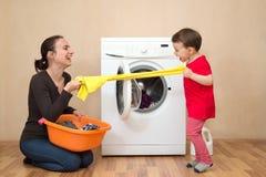 Mãe e daugher que jogam perto da máquina de lavar imagens de stock royalty free