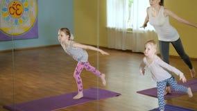 Mãe e daughtersr que fazem a ioga junto em um estúdio 4k da aptidão video estoque
