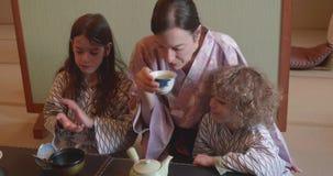 A mãe e duas crianças bebem o chá e comem-no em Ryokan em Japão vídeos de arquivo