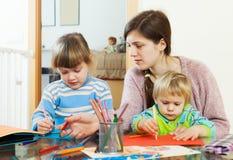 Mãe e duas crianças junto com lápis Imagem de Stock Royalty Free
