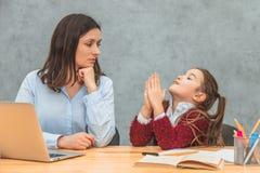 Mãe e estudante novas em um fundo cinzento Minhas mãos da filha acima de pedir que minha mãe olhe o portátil durante imagem de stock