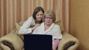 A mãe e a filha alegres apreciam a chamada video Olhe a tela e o sorriso do portátil, sentando-se em uma cadeira em casa vídeos de arquivo