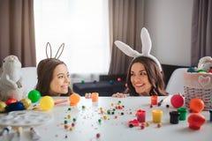 A mãe e a filha alegres positivas preparam-se para a Páscoa Jogam e escondem atrás da tabela na sala Mãe e filha fotografia de stock