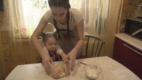 A mãe e a filha amassaram a massa elástica na cozinha video estoque