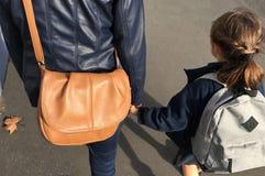 A mãe e a filha andam junto à escola fotos de stock