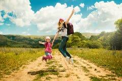A mãe e a filha andam na estrada através do campo Foto de Stock