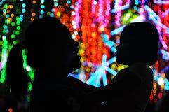 A mãe e a filha apreciam a exposição colorida das luzes de Natal na cidade de Makati, Filipinas foto de stock