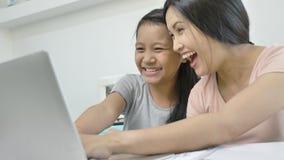A mãe e a filha asiáticas felizes da família estão usando o portátil em casa video estoque