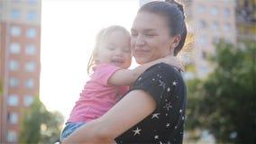 Mãe e filha bonitas fora Mum bonito e sua criança que jogam no parque junto Riso da mamã e do bebê filme
