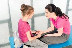 Mãe e filha bonitas no sportswear que senta-se na esteira da ioga imagem de stock royalty free