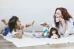 Mãe e filha bonitas novas da mulher com os pratos do brinquedo, doces Foto de Stock
