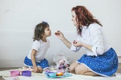Mãe e filha bonitas novas da mulher com os pratos do brinquedo, doces Fotos de Stock
