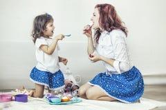 Mãe e filha bonitas novas da mulher com os pratos do brinquedo, doces Imagens de Stock