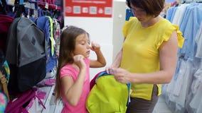 A mãe e a filha caucasianos próximo compram as prateleiras que escolhem a trouxa do saco de escola no mercado das miudezas filme