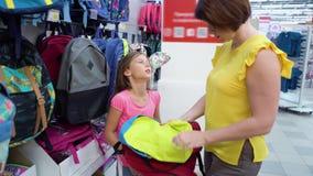 A mãe e a filha caucasianos próximo compram as prateleiras que escolhem a trouxa do saco de escola no mercado das miudezas vídeos de arquivo