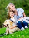 A mãe e a filha com cão estão na grama Fotos de Stock Royalty Free