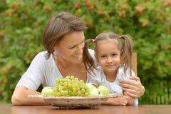 Mãe e filha com frutos Fotos de Stock