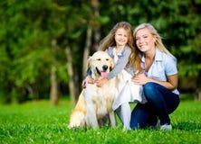 A mãe e a filha com Labrador estão na grama verde Imagens de Stock Royalty Free