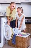 Mãe e filha com máquina de lavar Imagem de Stock