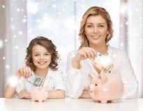 Mãe e filha com mealheiros e dinheiro Imagens de Stock Royalty Free