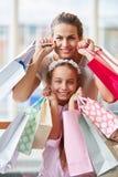 Mãe e filha com muitos sacos de compras fotografia de stock