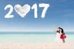 Mãe e filha com número 2017 na praia Foto de Stock