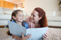Mãe e filha com o periódico no assoalho foto de stock