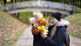 A mãe e a filha com os ramalhetes das folhas de outono são de fala e de riso no parque video estoque