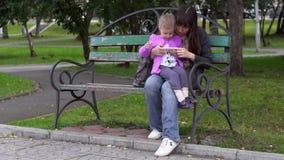 A mãe e a filha da família jogam usando um smartphone em um dia nebuloso no parque vídeos de arquivo