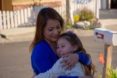 Mãe e filha de Latina que sorriem e que riem fora sob uma árvore fotografia de stock