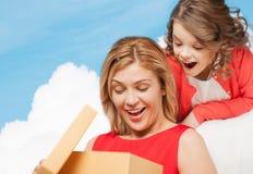 Mãe e filha de sorriso com caixa de presente imagem de stock