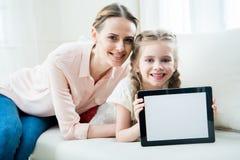 Mãe e filha de sorriso que mostram a tabuleta digital fotos de stock