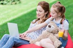 mãe e filha de sorriso que usa o portátil ao descansar no saco fotografia de stock royalty free