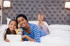 Mãe e filha de sorriso que usa a tabuleta digital ao encontrar-se na cama em casa fotografia de stock