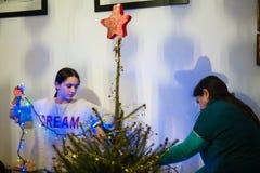 A mãe e a filha decoram a árvore de Natal Imagens de Stock