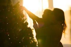 A mãe e a filha decoram uma árvore de Natal contra a janela imagens de stock royalty free