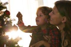 A mãe e a filha decoram uma árvore de Natal contra a janela foto de stock