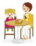 A mãe e a filha dos desenhos animados têm um almoço com uma tabela do café Fotografia de Stock Royalty Free