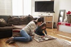 Mãe e filha em casa que olham através do álbum de fotografias fotografia de stock royalty free
